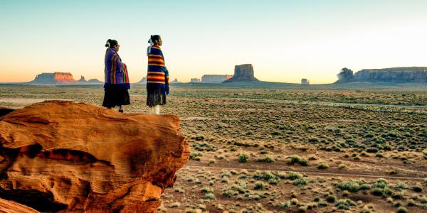 Two indigenous women stand on a rock overlooking a desert