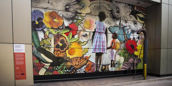 Mural by Lares Feliciano of young girl of color looking at flowers