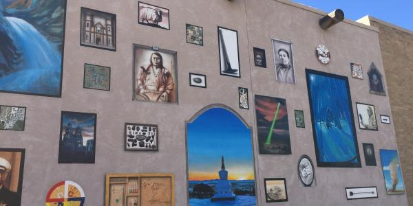 wall of museum in Alamosa covered in painted on paintings representing community heritage