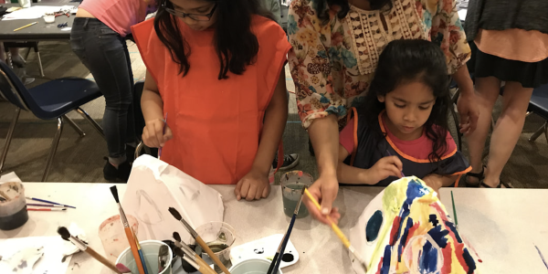 Two kids paint during a workshop.