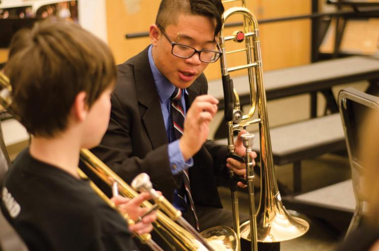 A CU Boulder student instructs a middle school musician.