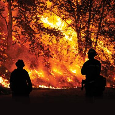 two firefighters standing in front of wildfire