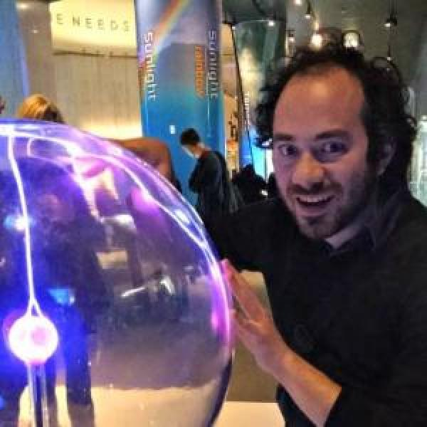 A photo of Mike with his hands on a plasma ball at a museum.