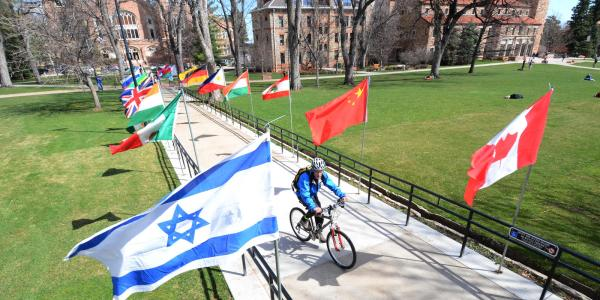bike riding through flags on campus