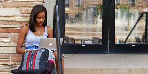 student working on computer on campus
