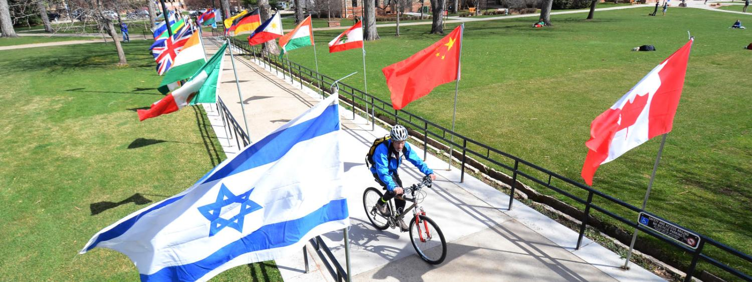 bike rider on campus going through international cwa flags