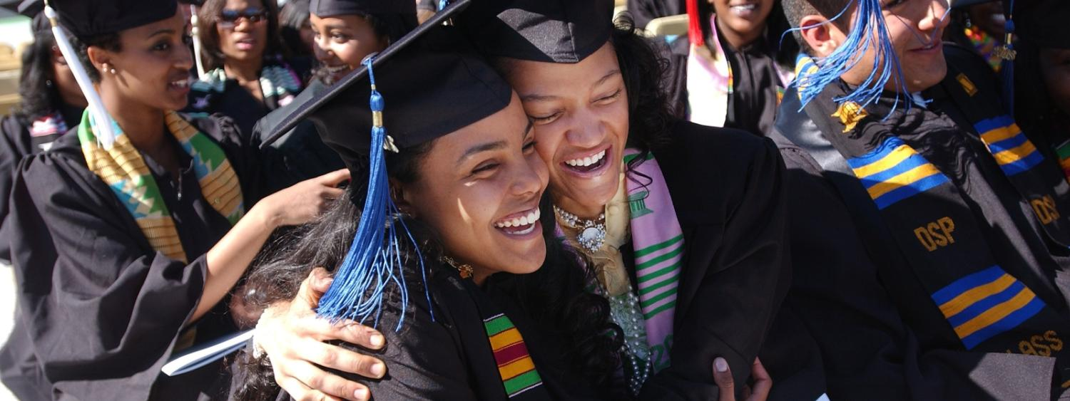 two students hugging at graduation wearing diversity scarves