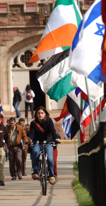 girl riding bike on campus near international flags