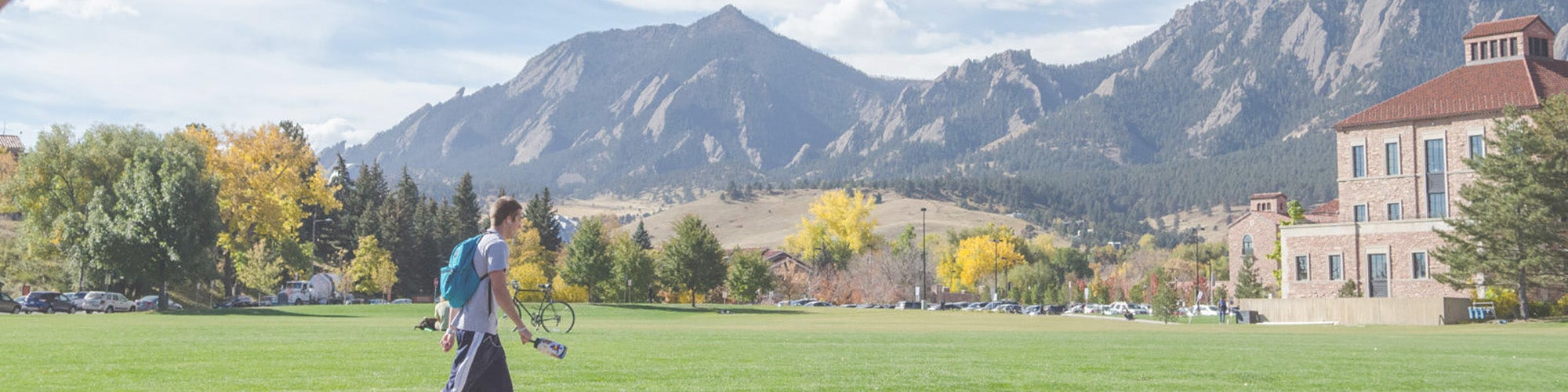 Student walking in front of the flatirons