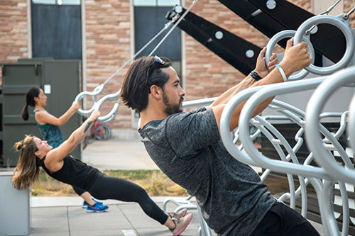 Students working out on outdoor fitness equipment