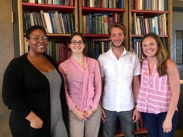 Simone Hyater-Adams, Allie Lau, Julian Gifford, Jessica Hoehn standing in front of bookshelves