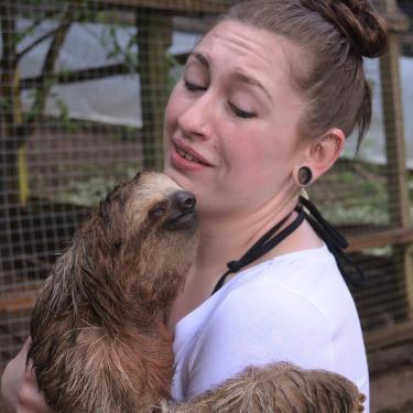 Katie Rainey holding and looking down lovingly at a sloth