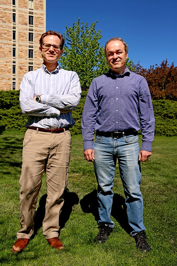 Portrait of Michael Hermele (Left) and Victor Gurarie (Right) standing in front of the JILA Tower.