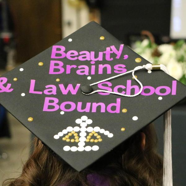 """Student wearing a decorated graduation cap. Cap reads, """"Beauty, Brains & Law School Bound""""."""