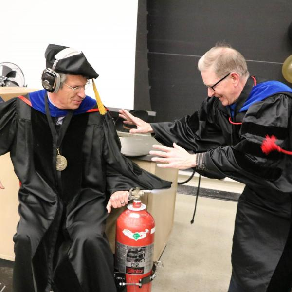 Professor Paul Beale performing demonstration on a wheeled cart with two fire extinguishers on either side.