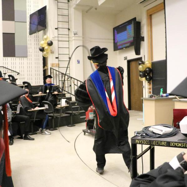 Professor Paul Beale performing demonstration in a cowboy hat with a whip.