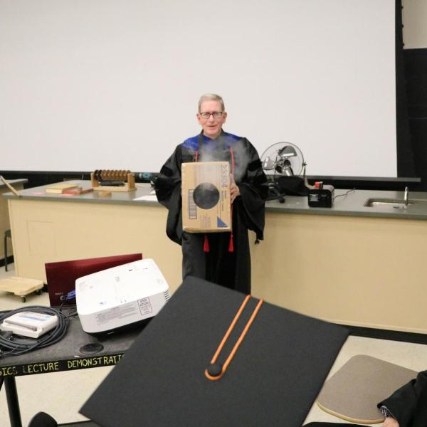 Professor Mike Dubson performing physics demonstration by blowing smoke rings from a cardboard box.