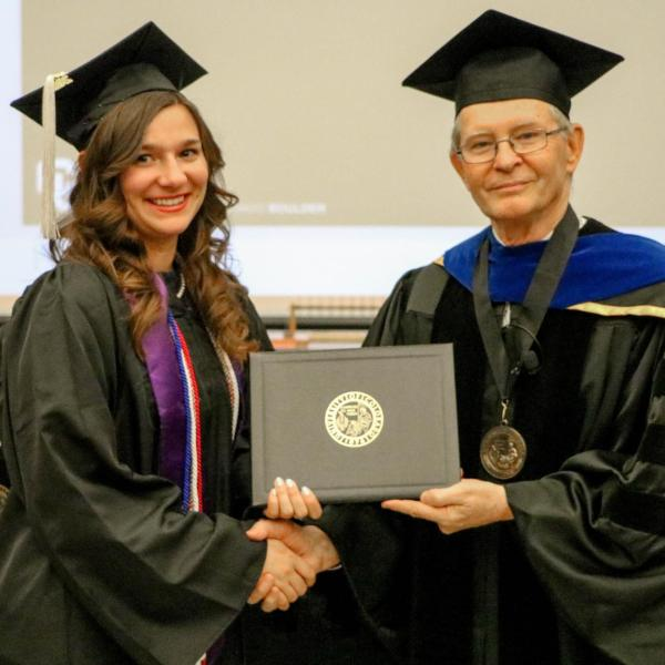 Undergraduate Katerina Overburg receiving diploma cover.