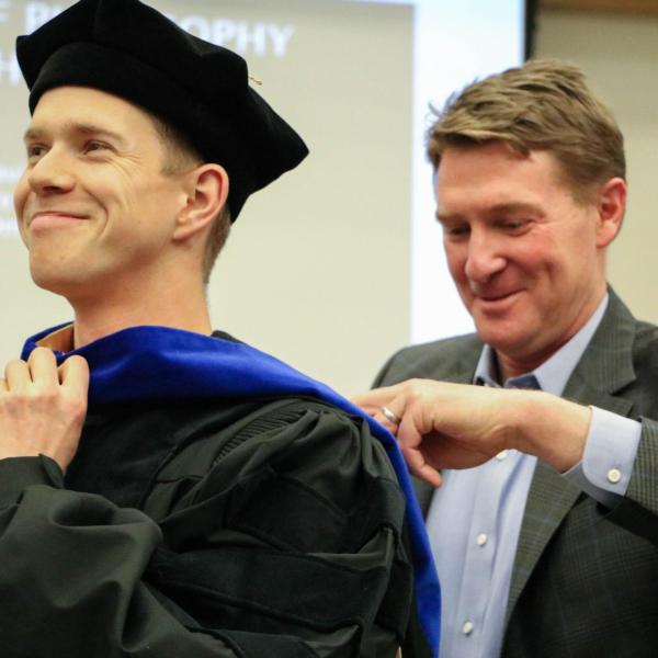 PhD Candidate Daniel Cole being hooded.