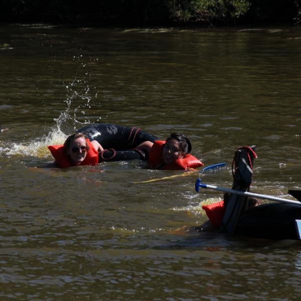 PLC students swim for the other side of the pond after their makeshift raft fails to hold them above water
