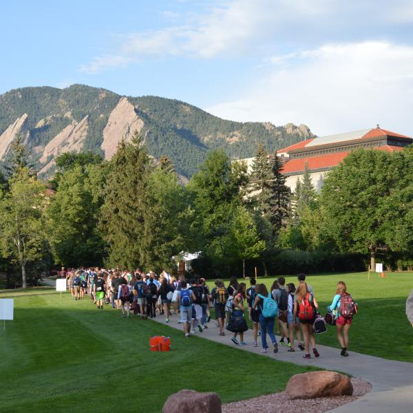 Students walk through the Norlin Quad to get to the buses that will take them to orientation