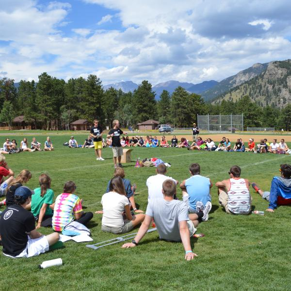 Orientation attendees gather on the activity fields at the YMCA camp of the Rockies for a group challenge
