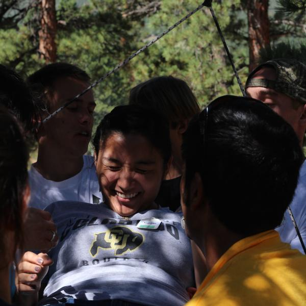 PLCer Martin Garcia winces as he tries to avoid touching the spider web in a low ropes initiative