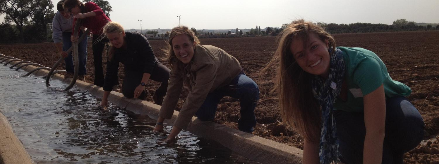 PLC students working with an irrigation ditch which is full of water