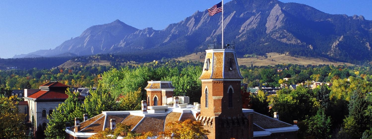 Aerial photo of Old Main building with Flatirons in the background.