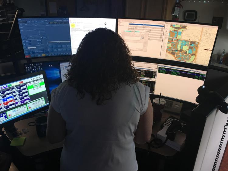 A dispatcher sits in front of multiple computer monitors while working in the CUPD dispatch center