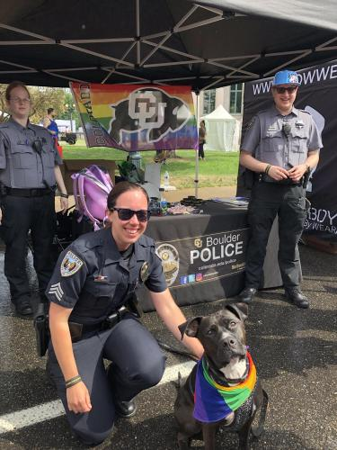 Sgt. Vekasy poses with a dog wearing a rainbow scarf at Denver Pride 2019
