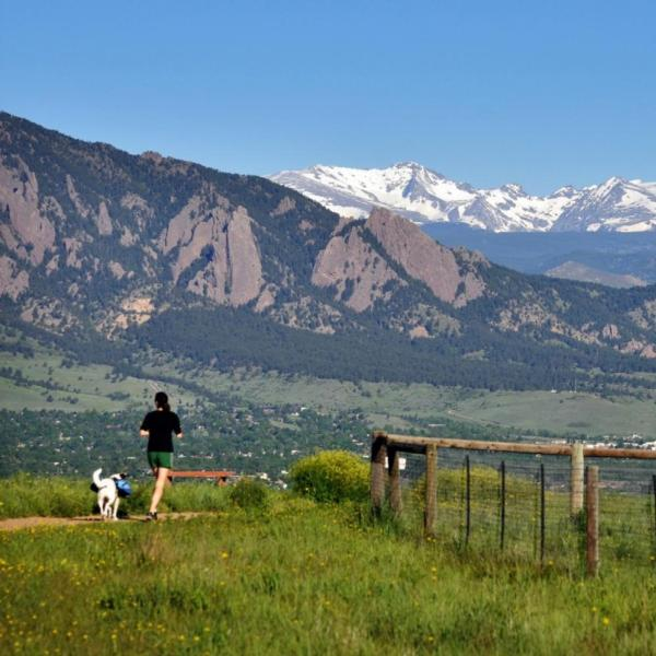 Student running with dog along trail outside of Boulder
