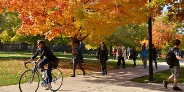 Students walking and biking between classes during the fall