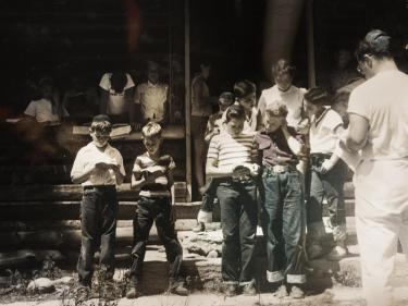 Black and white photo of a group of children camp-goers reading from their prayer books. In the right corner, a man in all white appears to be leading everyone.