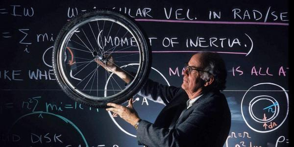 person with a bicycle wheel in front of a chalkboard
