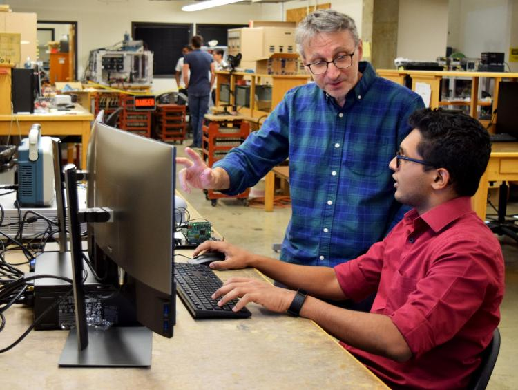 A student and teacher talking by a computer in a lab.