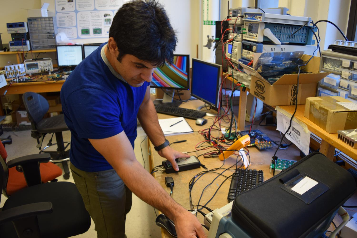 A student adjusts an oscilliscope on his lab bench in the CoPEC lab
