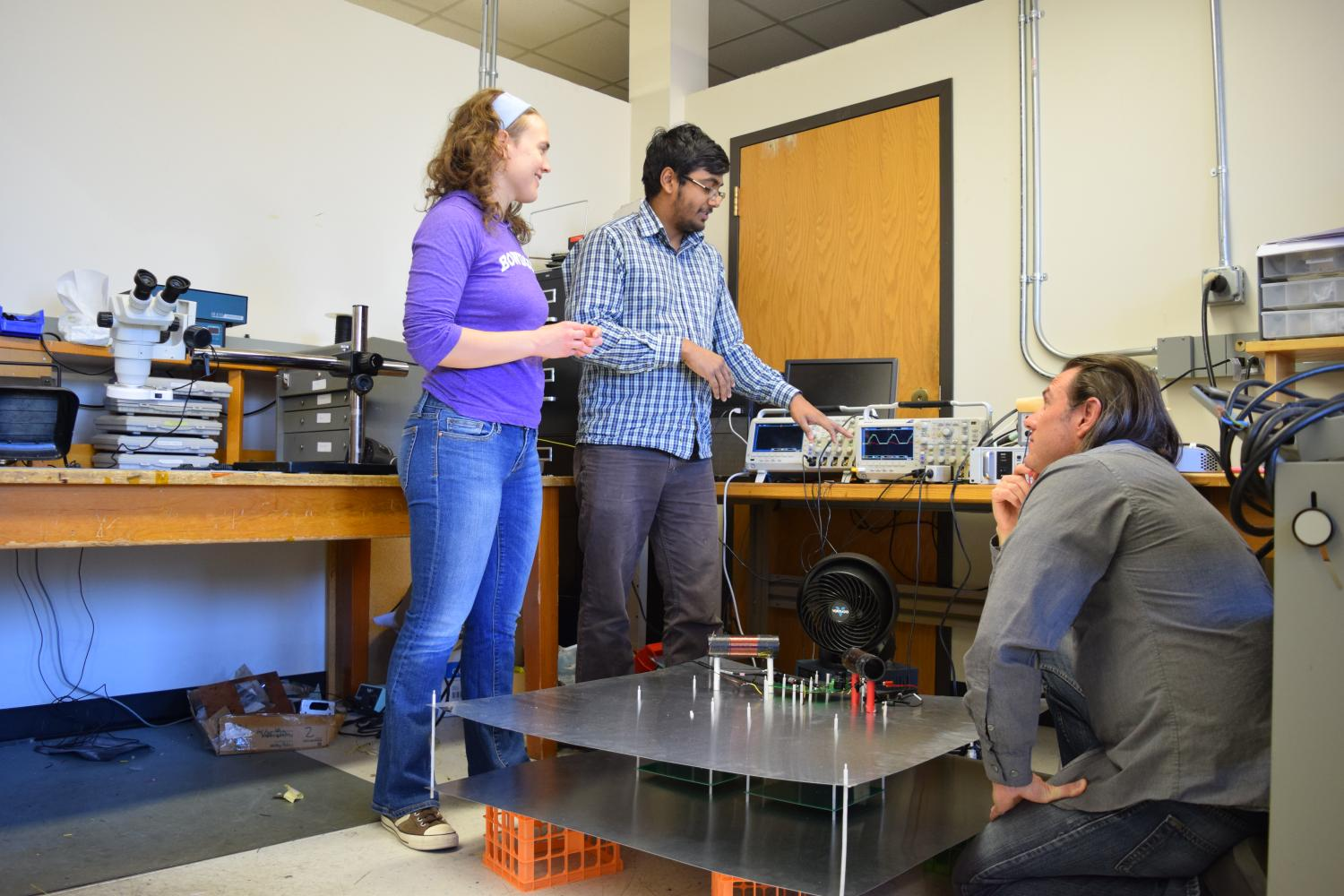 Three graduate students discuss a project in the CoPEC lab