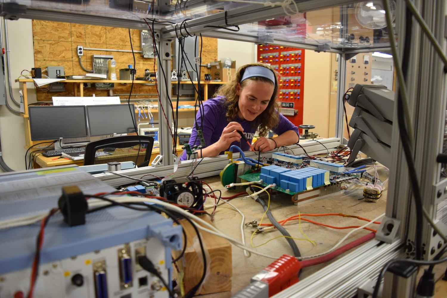 A student leans over her project to make an adjustment in the CoPEC lab