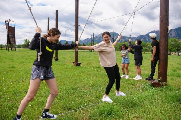 PCDP Bridge students working together on a ropes course