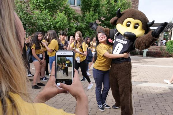 a student posing with Chip the buffalo, CU's costumed mascot