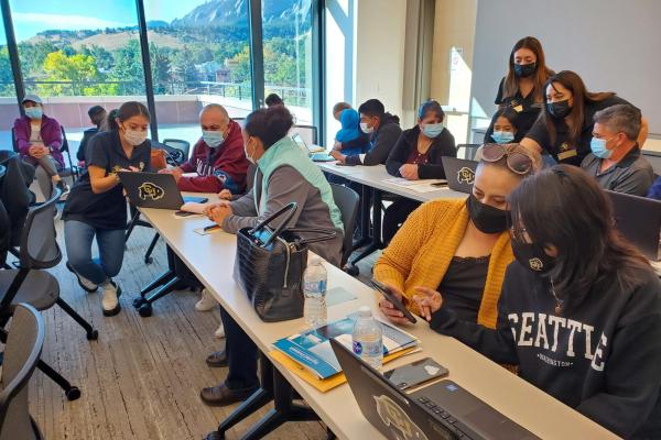 a classroom full of PCDP students and their parents working on financial aid applications during a Saturday academy