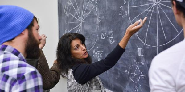 Professor writes equations on blackboard while students watch