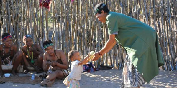 woman handing girl fruit