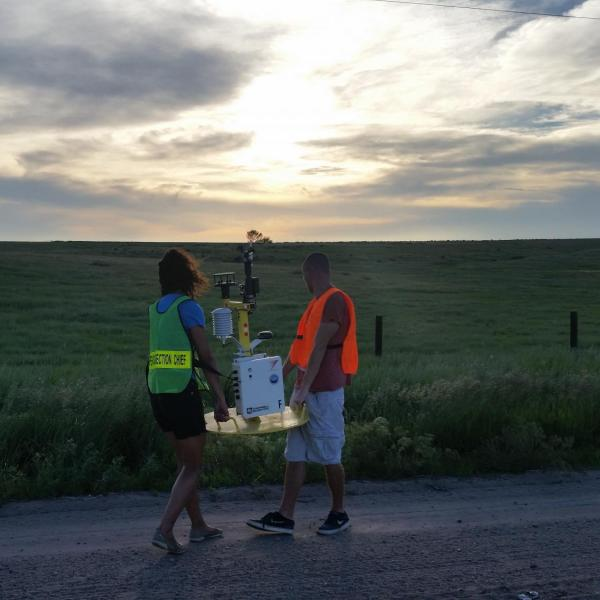 "CSWR intern students deploying a weather ""pod"" on a county road in Kansas/Nebraska in preparation for a passing convective system as part of the PECAN project on 1 June 2015. The weather pod collects meteorological data (wind, temperature, dew point, pressure), which will later be analyzed by graduate students and researchers to understand how nocturnal thunderstorms behave."