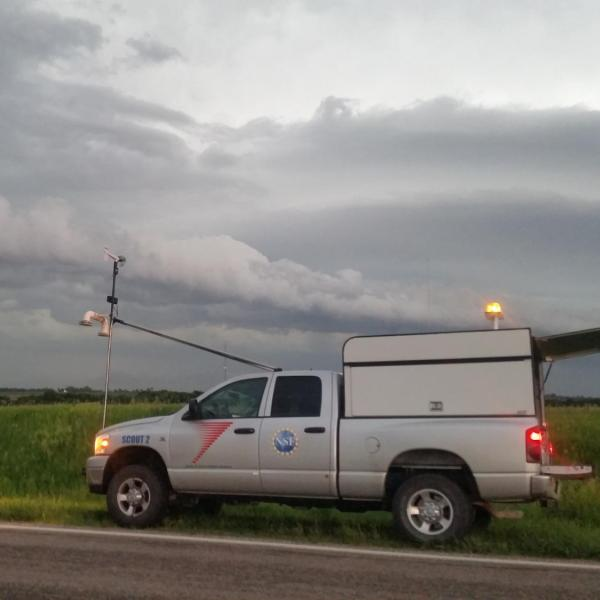 A Center for Severe Weather Research (CSWR) scout vehicle instrumented with weather instruments waiting for a mesoscale convective system (MCS) to move over its location during the PECAN field project on 10 June 2015.