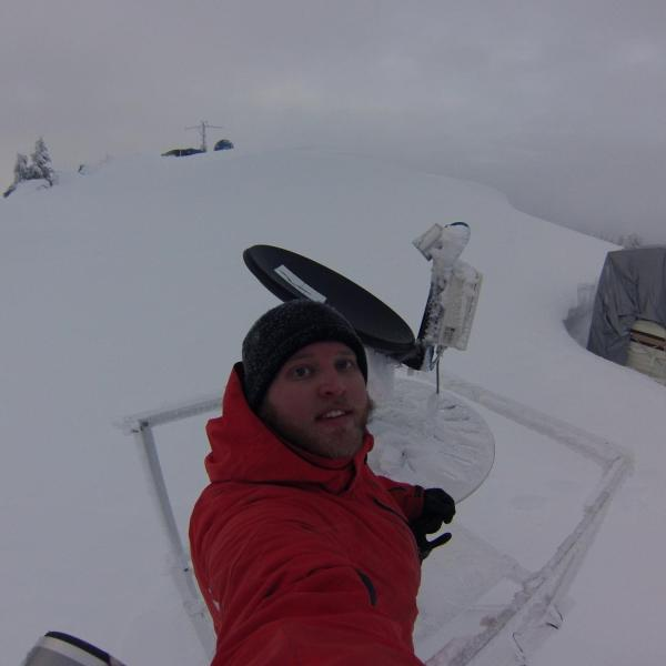 Graduate student Josh Aikins de-icing instruments from a mountaintop location (7,000 ft elevation) in Idaho on 21 January 2017 during the Seeded and Natural Orographic Wintertime clouds -the Idaho Experiment (SNOWIE) filed campaign. The tarp-covered trailer buried in snow was the lodging accommodations for 2 people throughout the project (January - March 2017).