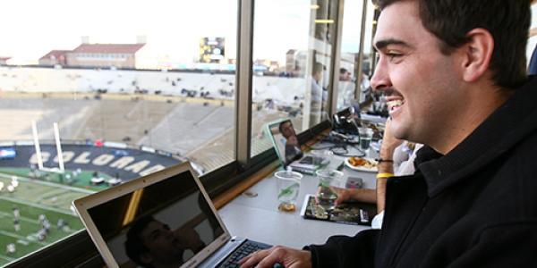 Journalist in the press box in Folsom Field at CU Boulder