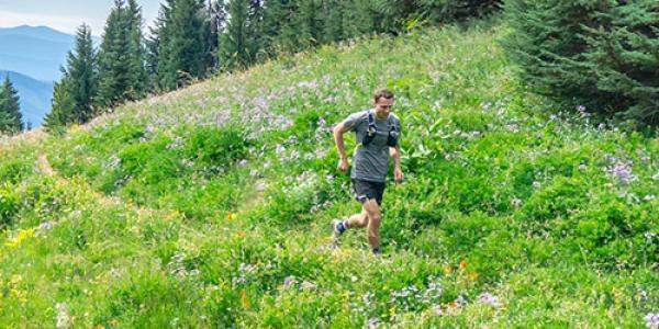 man running on a bright green mountainside