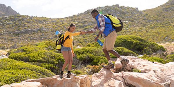 African American couple helps each other while hiking